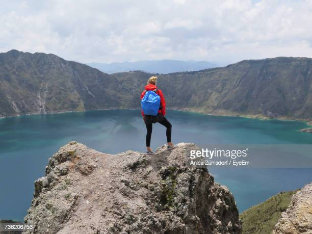 rear view of woman standing on rock formation while looking at lake - ecuador fotografías e imágenes de stock