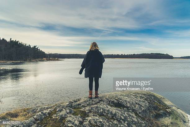 rear view of woman standing on rock in lake against sky - long coat stock pictures, royalty-free photos & images