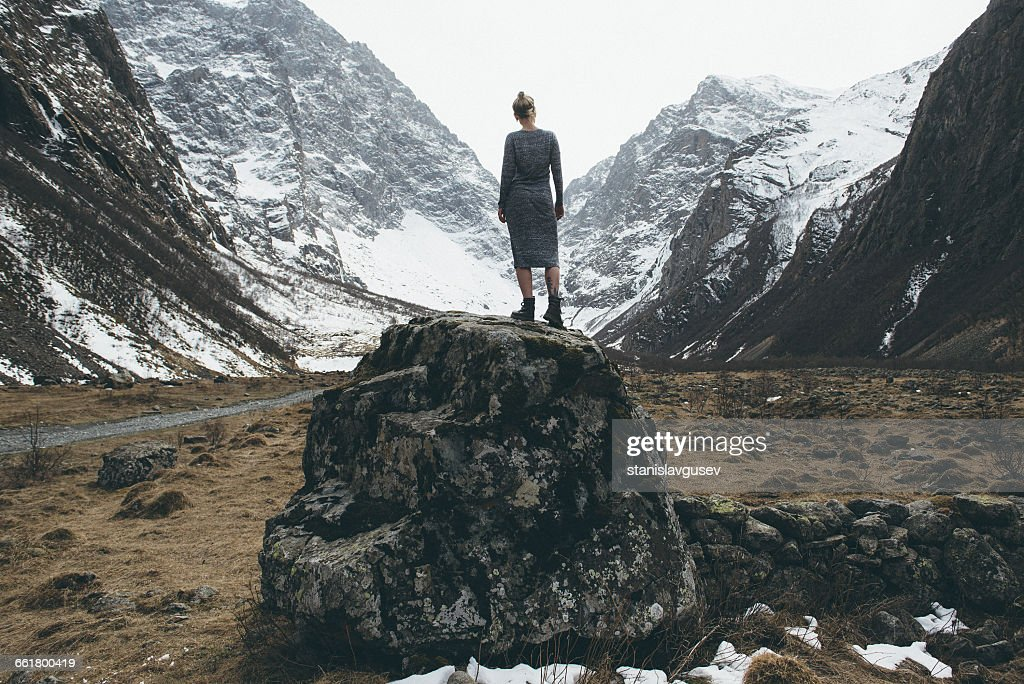 Rear view of woman standing on rock, North Ossetia, Russia : Stock Photo