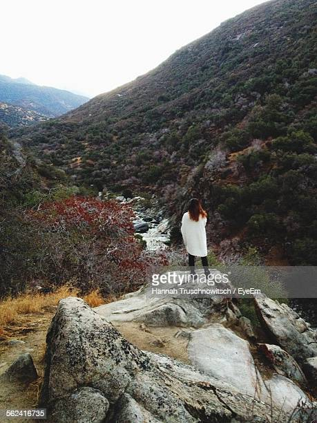 rear view of woman standing on rock - hannah brooks stock pictures, royalty-free photos & images