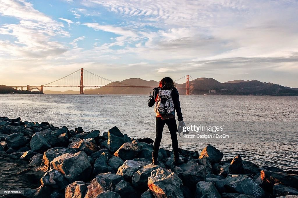 Rear View Of Woman Standing On Rocks By Sea Against Golden Gate Bridge During Sunset : Stock Photo