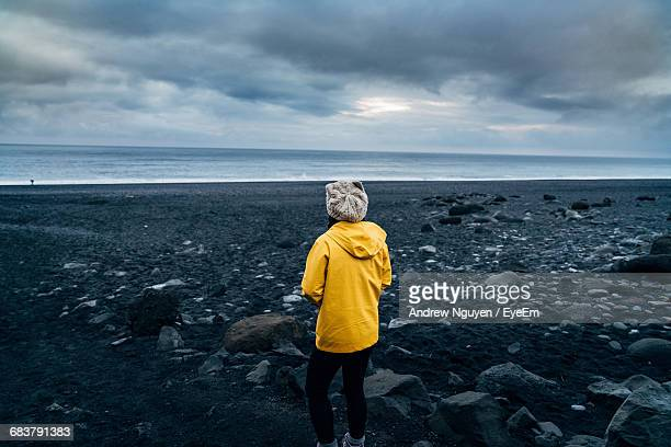 Rear View Of Woman Standing On Rocky Beach