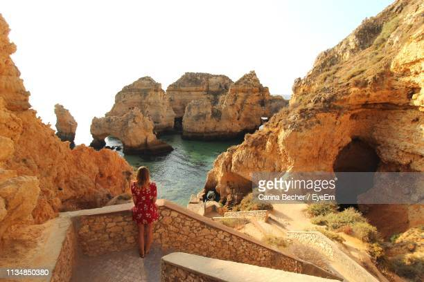 rear view of woman standing on rocky shore against clear sky - portugal stock pictures, royalty-free photos & images