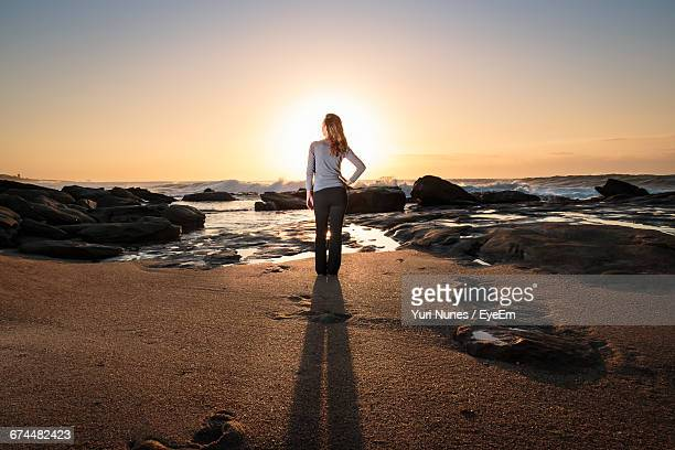 Rear View Of Woman Standing On Shore At Beach Against Sky During Sunrise