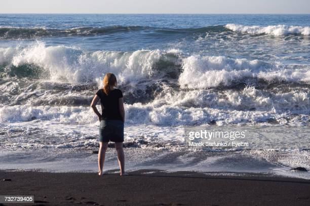 rear view of woman standing on shore at beach - marek stefunko stock photos and pictures