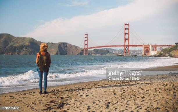 rear view of woman standing on shore with golden gate bridge in background - bortes stockfoto's en -beelden