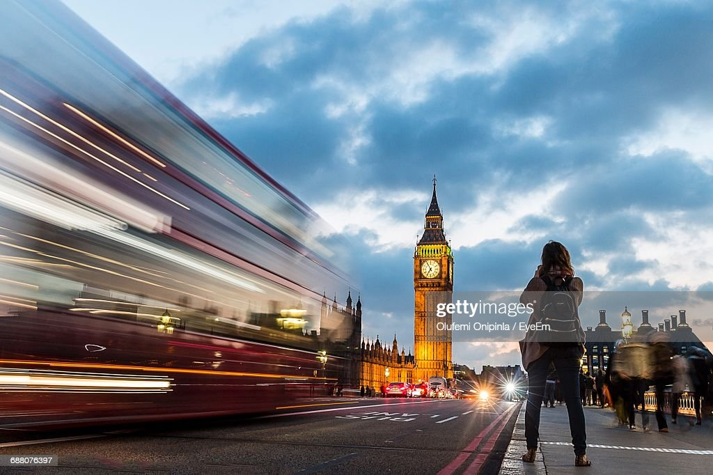 Rear View Of Woman Standing On Sidewalk By Bus And Big Ben Against Cloudy Sky During Sunset : Stock-Foto