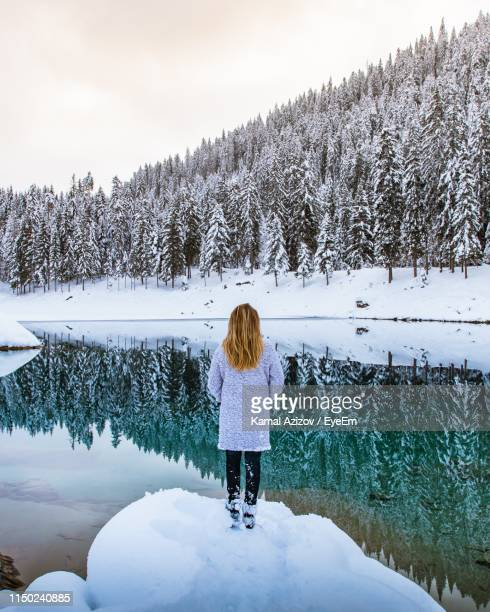 rear view of woman standing on snow by lake in forest during winter - switzerland stock pictures, royalty-free photos & images