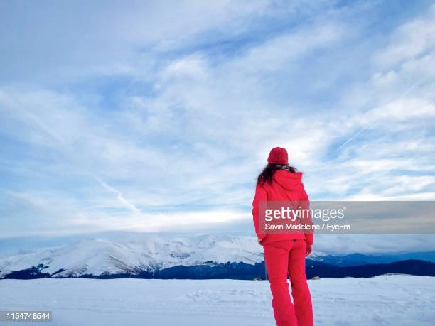 rear view of woman standing on snowcapped mountain against sky - lady madeleine stock-fotos und bilder