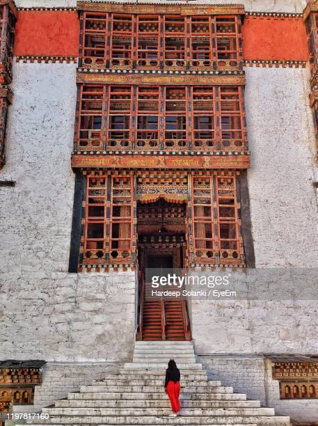 rear view of woman standing on staircase - thimphu stock pictures, royalty-free photos & images