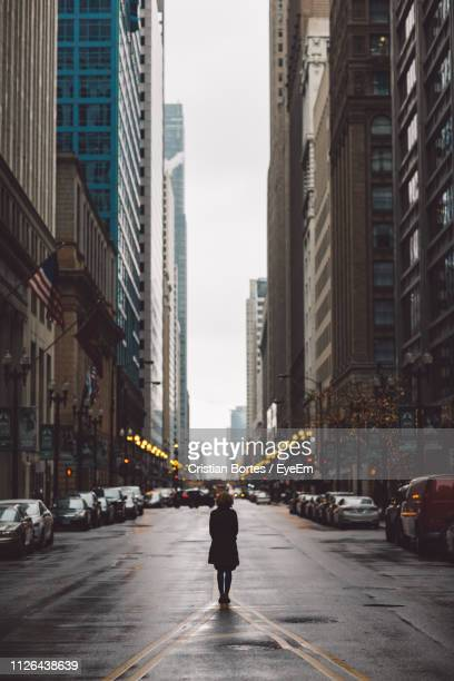 rear view of woman standing on street amidst buildings in city - bortes stock-fotos und bilder