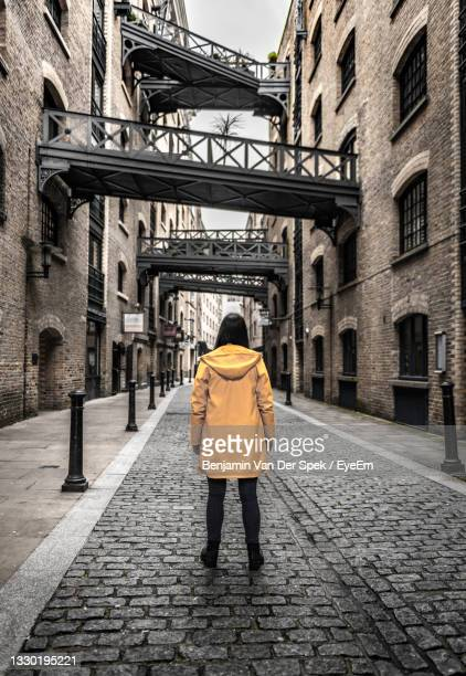 rear view of woman standing on street amidst buildings - back stock pictures, royalty-free photos & images