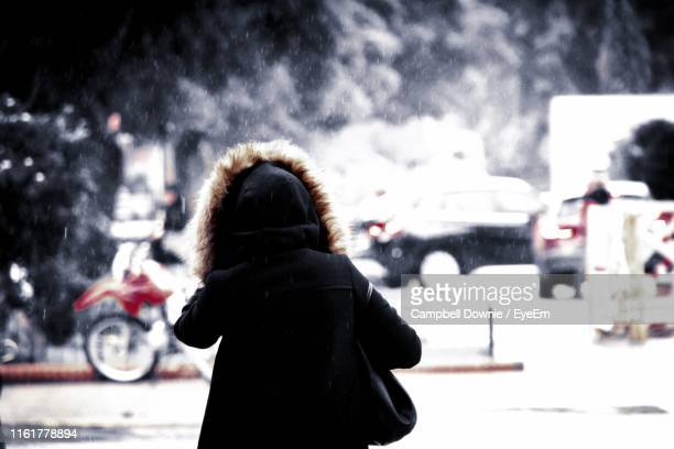 rear view of woman standing on street in city during winter - campbell downie stock pictures, royalty-free photos & images