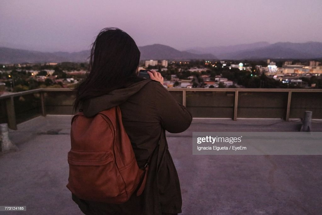 Rear View Of Woman Standing On Terrace In City At Dusk : Photo