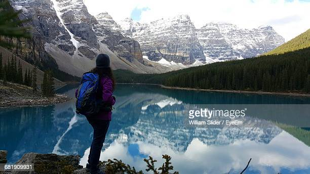 rear view of woman standing on the edge of lake louise - lake louise stock photos and pictures