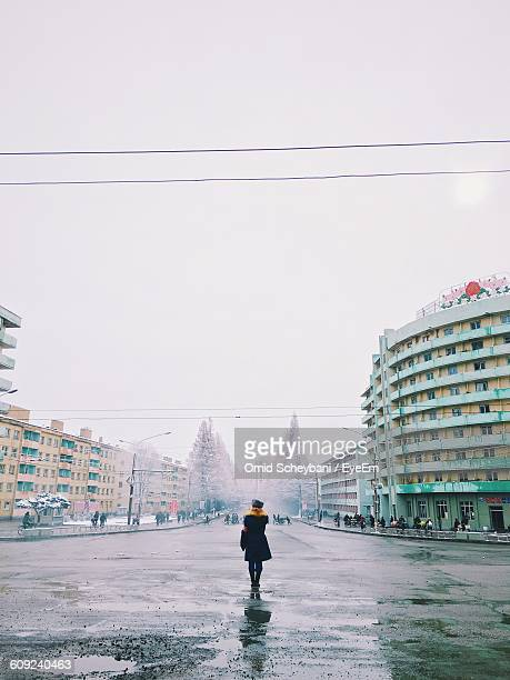 Rear View Of Woman Standing On Wet Road Amidst Buildings Against Sky