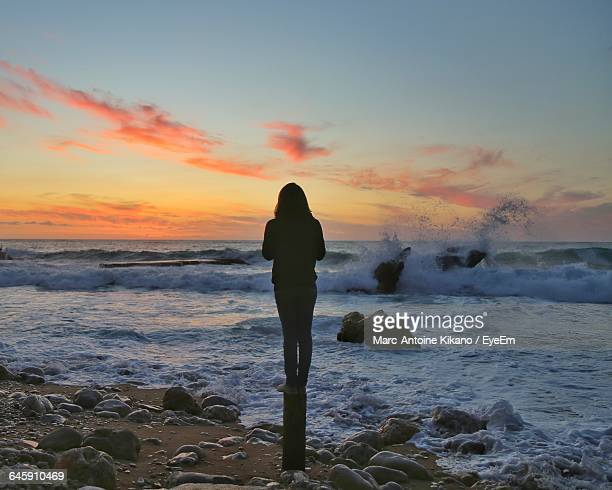 Rear View Of Woman Standing On Wooden Post By Sea During Sunset