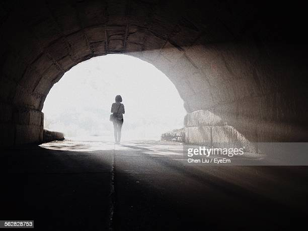 rear view of woman standing outside of tunnel - light at the end of the tunnel stock pictures, royalty-free photos & images