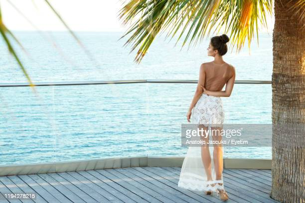 rear view of woman standing palm tree against sea - チュール生地 ストックフォトと画像