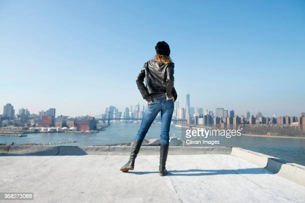 rear view of woman standing with hands in pockets against clear blue sky - hands in pockets stock pictures, royalty-free photos & images