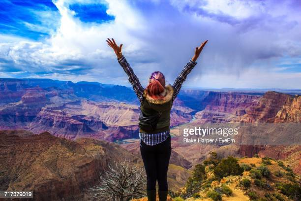 Rear View Of Woman Standing With Raised Hands At Grand Canyon National Park Against Sky