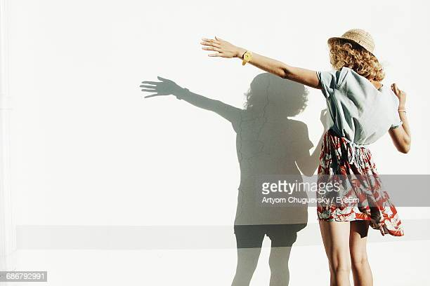 rear view of woman standing with shadow on white wall - in front of stock photos and pictures
