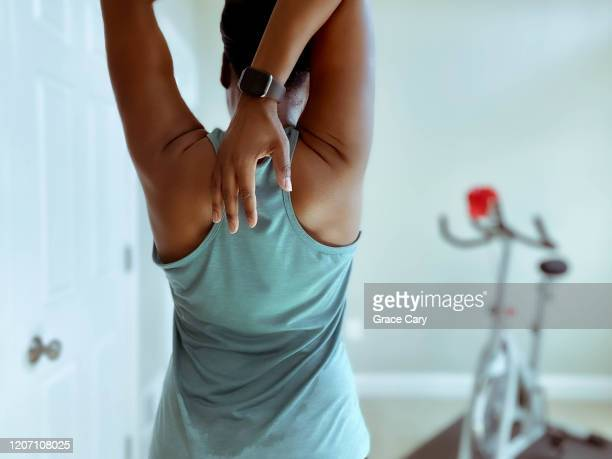 rear view of woman stretching after indoor cycling - wellness stock pictures, royalty-free photos & images