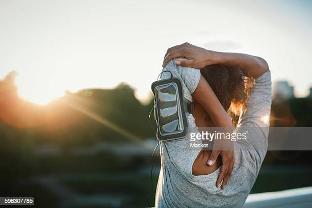 rear view of woman stretching arm at park - armband stock pictures, royalty-free photos & images