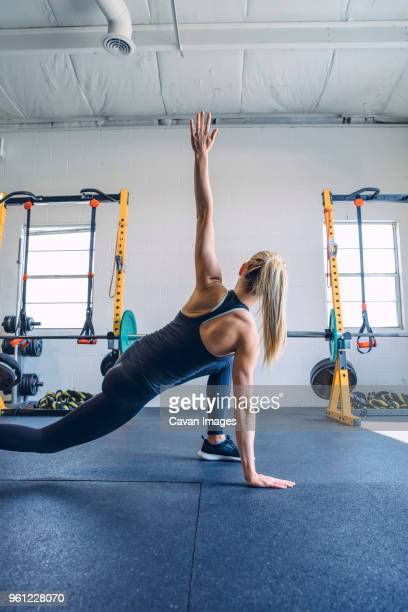 rear view of woman stretching arms while exercising against wall in gym - warm up exercise stock pictures, royalty-free photos & images