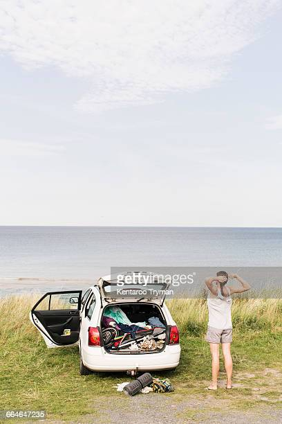 Rear view of woman stretching by car on field against sea