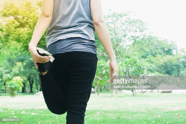 Rear View Of Woman Stretching Leg At Park