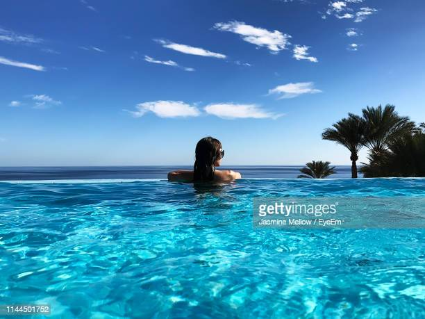 rear view of woman swimming in infinity pool against sky - シャルムエルシェイク ストックフォトと画像
