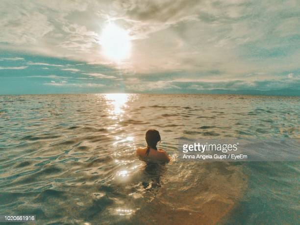 Rear View Of Woman Swimming In Sea Against Cloudy Sky