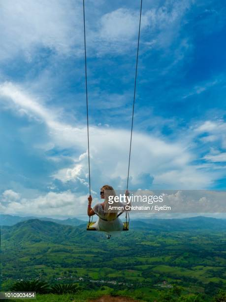 rear view of woman swinging against landscape and sky - 揺らす ストックフォトと画像
