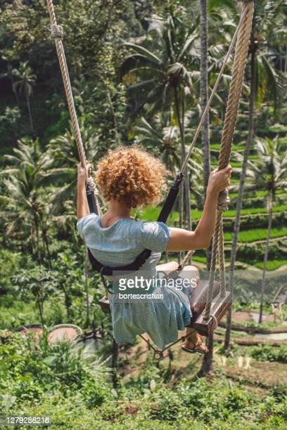 rear view of woman swinging in forest - bortes stock-fotos und bilder