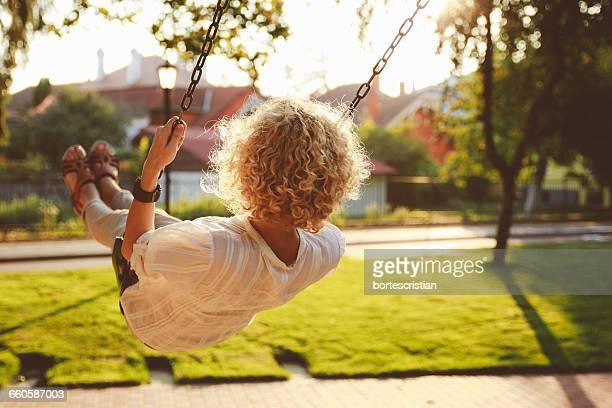 rear view of woman swinging in park - bortes fotografías e imágenes de stock