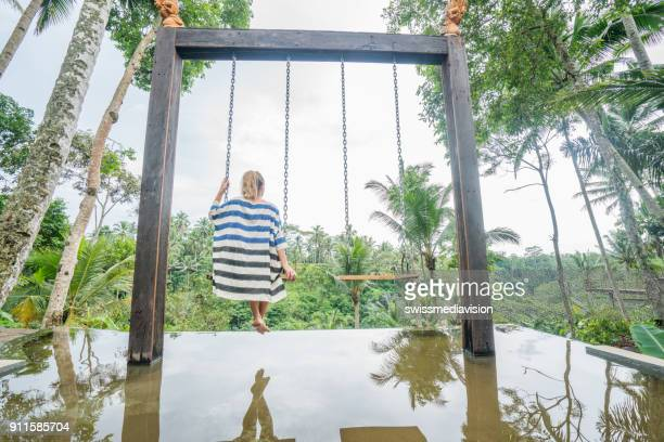 Rear view of woman swinging in tropical climate, Indonesia