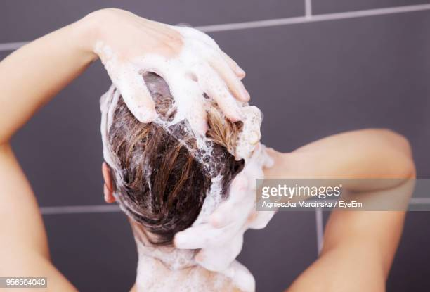 rear view of woman taking bath in bathroom - shampoo stockfoto's en -beelden