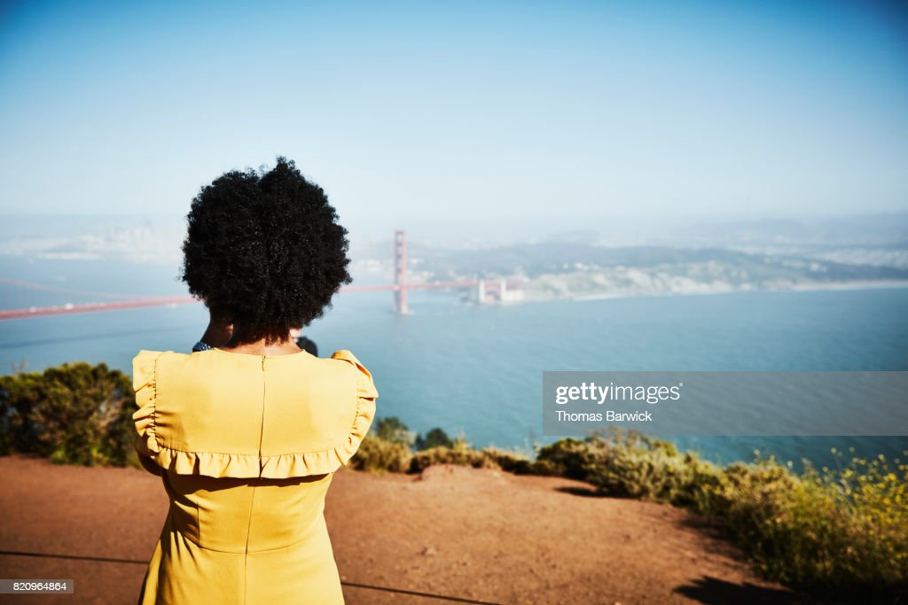 Rear view of woman taking photo of Golden Gate Bridge from overlook : Stock Photo