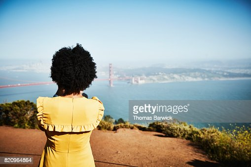 Rear view of woman taking photo of Golden Gate Bridge from overlook