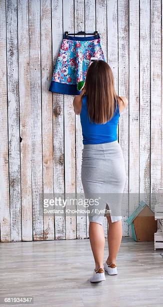 Rear View Of Woman Taking Photograph Of Skirt