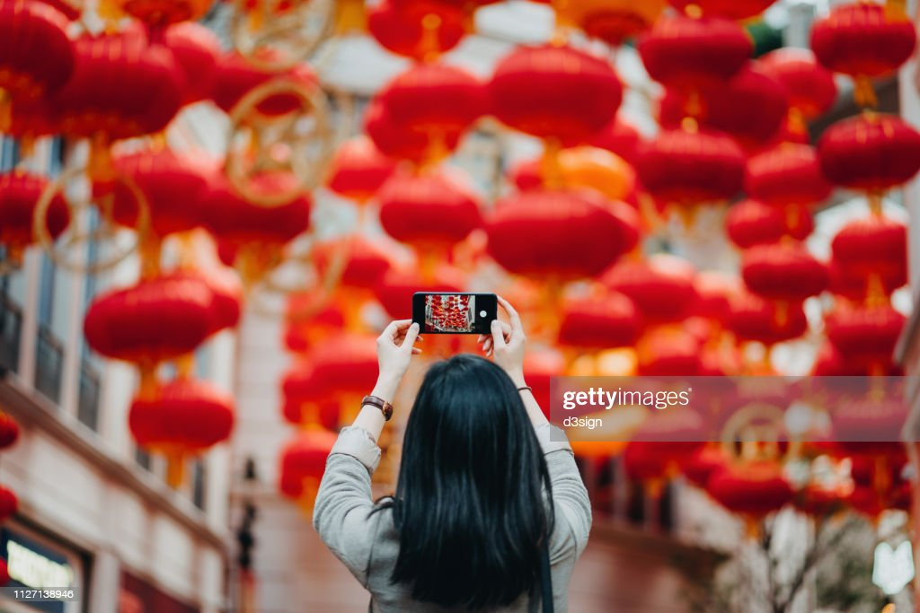 Rear view of woman taking photos of traditional Chinese red lanterns with smartphone on city street : Stock Photo