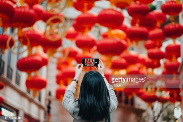 rear view of woman taking photos of traditional chinese red lanterns with smartphone on city street - culturen stockfoto's en -beelden