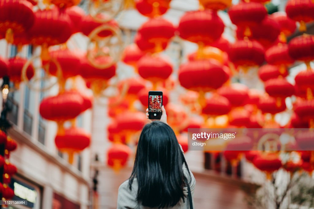 Rear view of woman taking photos of traditional Chinese red lanterns with smartphone on city street : Foto stock