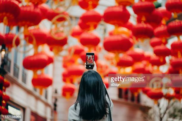 rear view of woman taking photos of traditional chinese red lanterns with smartphone on city street - toerisme stockfoto's en -beelden