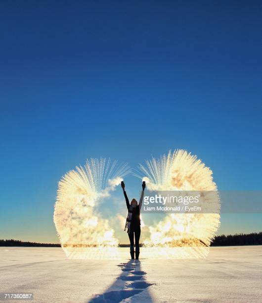 Rear View Of Woman Throwing Powder Snow While Standing On Landscape Against Clear Blue Sky