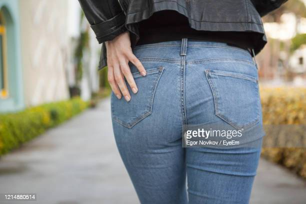 rear view of woman touching jeans pocket while standing outdoors - buttock photos stock pictures, royalty-free photos & images