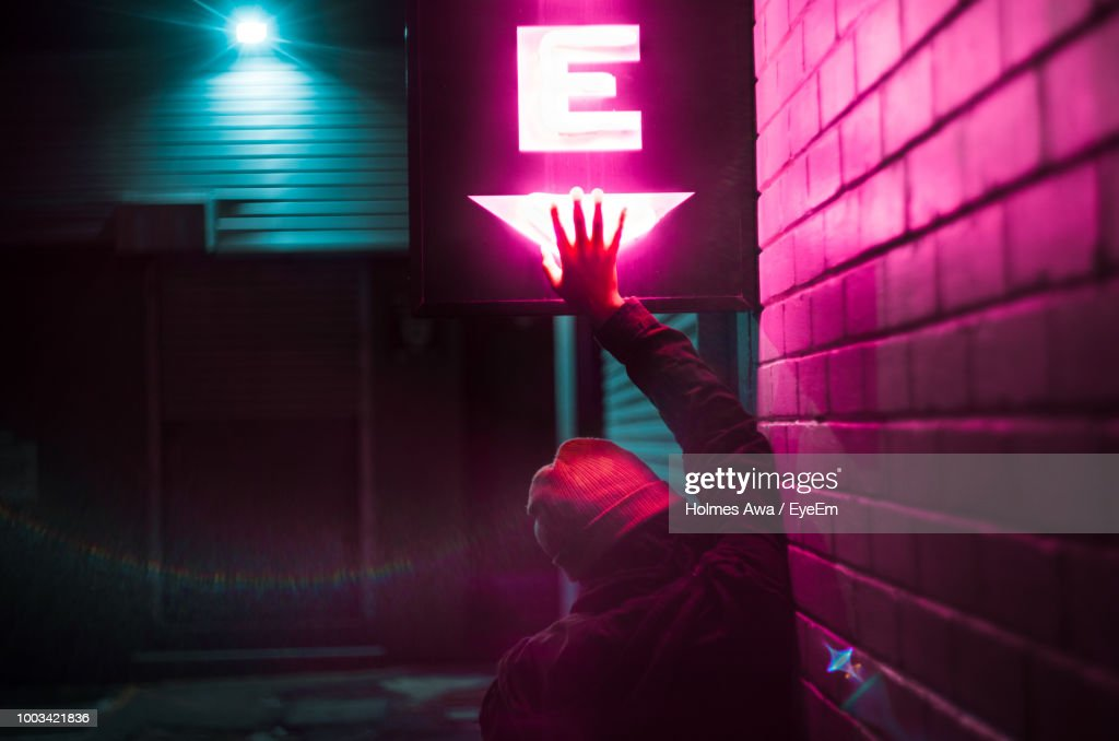 Rear View Of Woman Touching Neon Sign By Wall At Night : Stock Photo