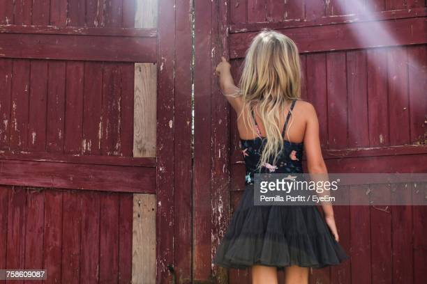 Rear View Of Woman Touching Old Closed Gate