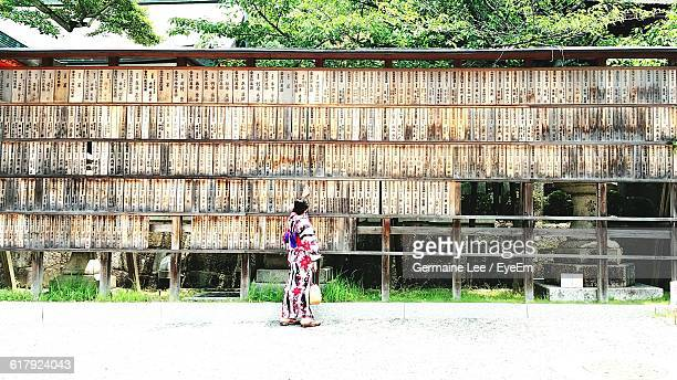 rear view of woman touching text on wooden wall at fushimi inari shrine - shinto shrine stock pictures, royalty-free photos & images